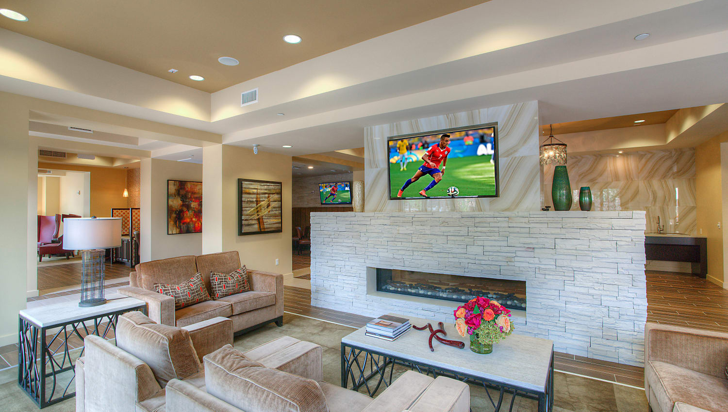 Flatscreen TV above the fireplace in the clubhouse lounge at Vistara at SanTan Village in Gilbert, Arizona