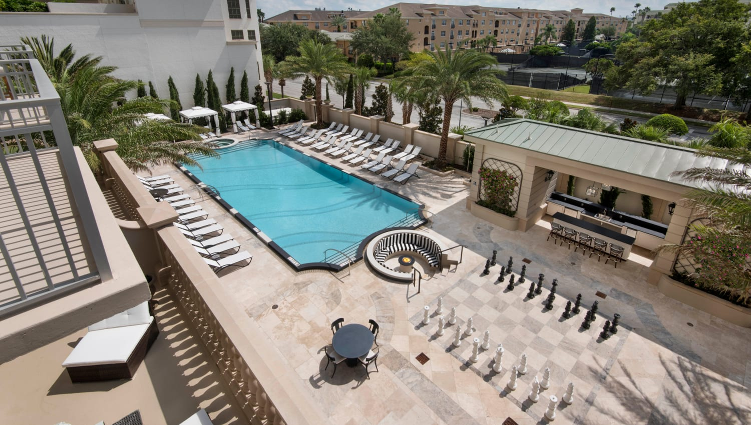 View of the swimming pool area and life-size chess board from an upper-floor home at Olympus Harbour Island in Tampa, Florida
