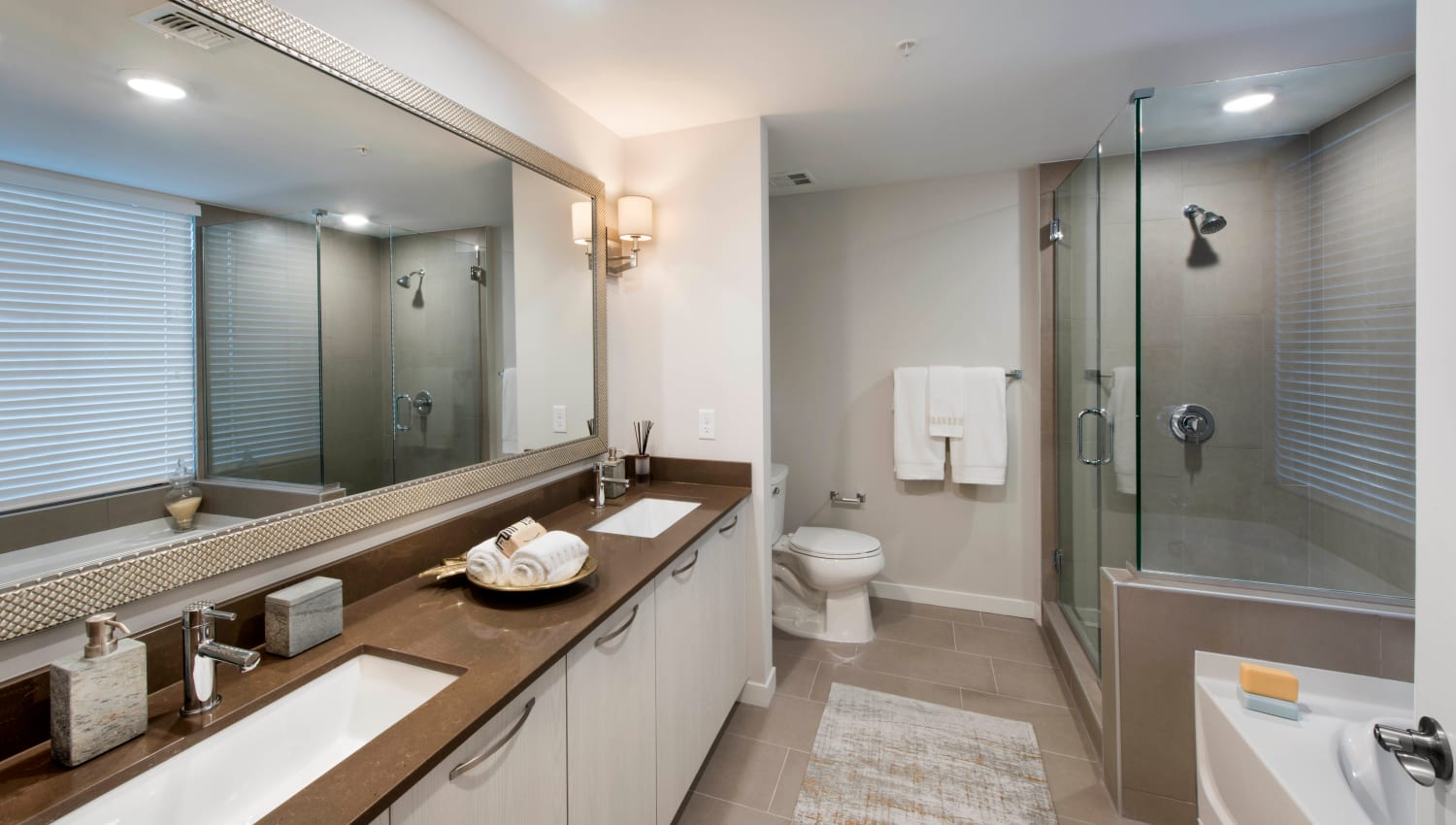 Spacious quartz countertop and dual sinks in the master bathroom of a model luxury apartment at Olympus Harbour Island in Tampa, Florida