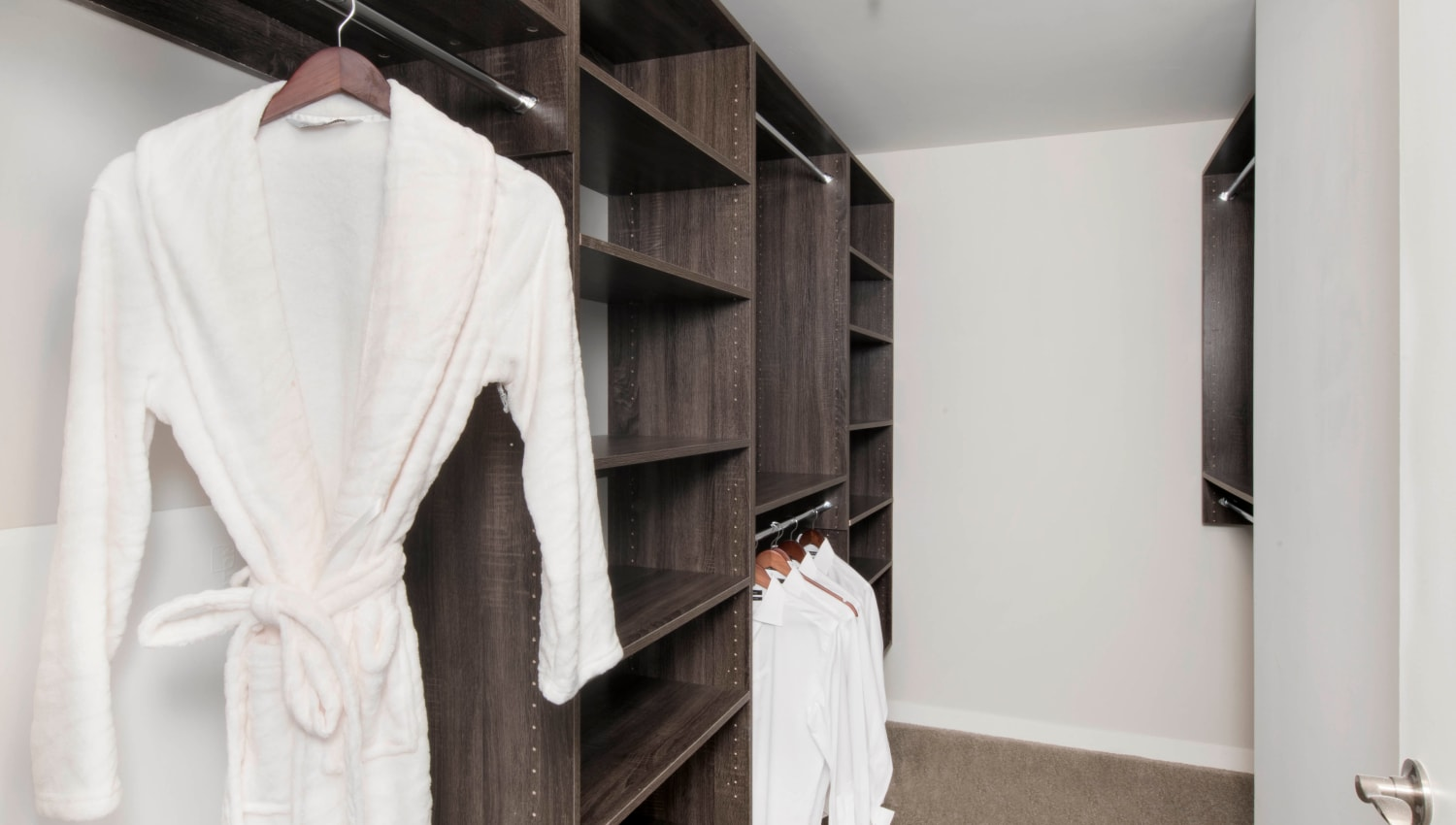 Large walk-in closet with custom built-in shelving in a model home's bedroom at Olympus Harbour Island in Tampa, Florida