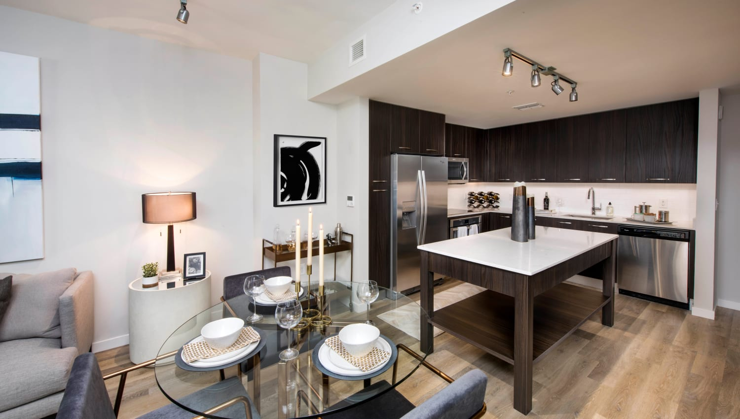 Dining and kitchen areas in the open-concept floor plan of a model home at Olympus Harbour Island in Tampa, Florida