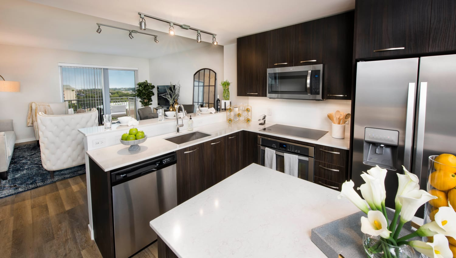 View of the dining and living areas over the breakfast bar in a model apartment's kitchen at Olympus Harbour Island in Tampa, Florida