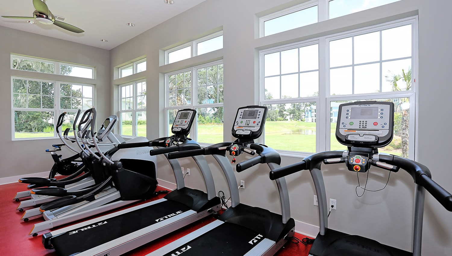 Row of treadmills in the fitness center with a view of the property outside at The Slate in Savannah, Georgia