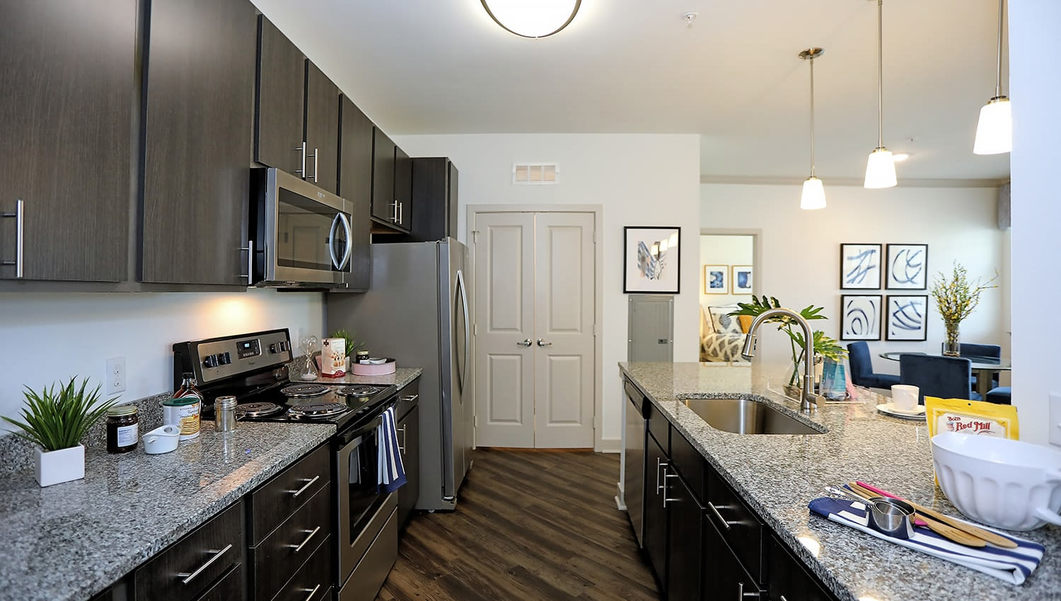 Model apartment kitchen with hardwood flooring at The Slate in Savannah, Georgia
