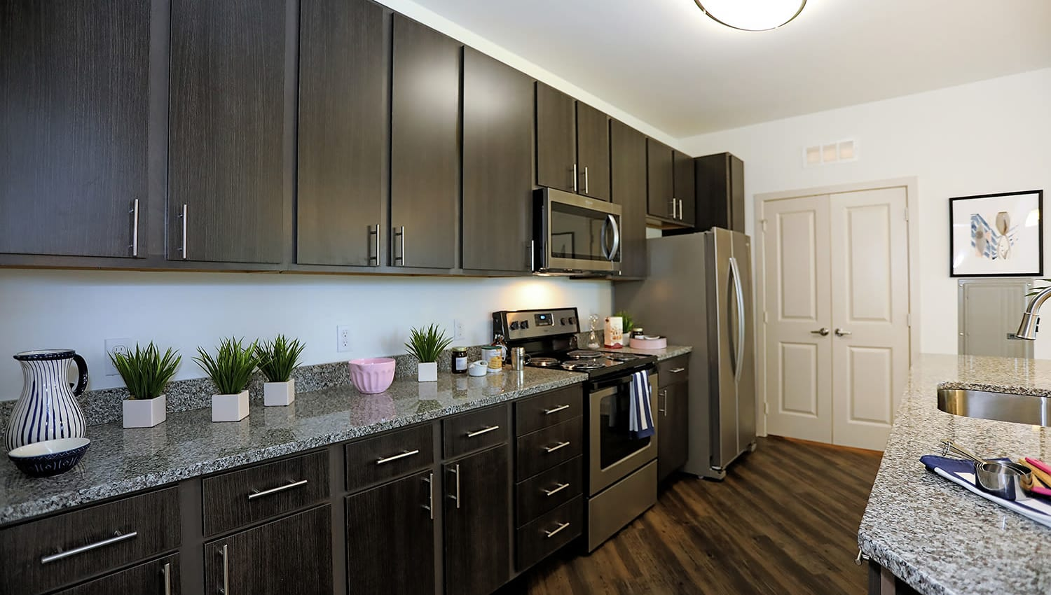 Espresso wood cabinetry in a model apartment's gourmet kitchen at The Slate in Savannah, Georgia