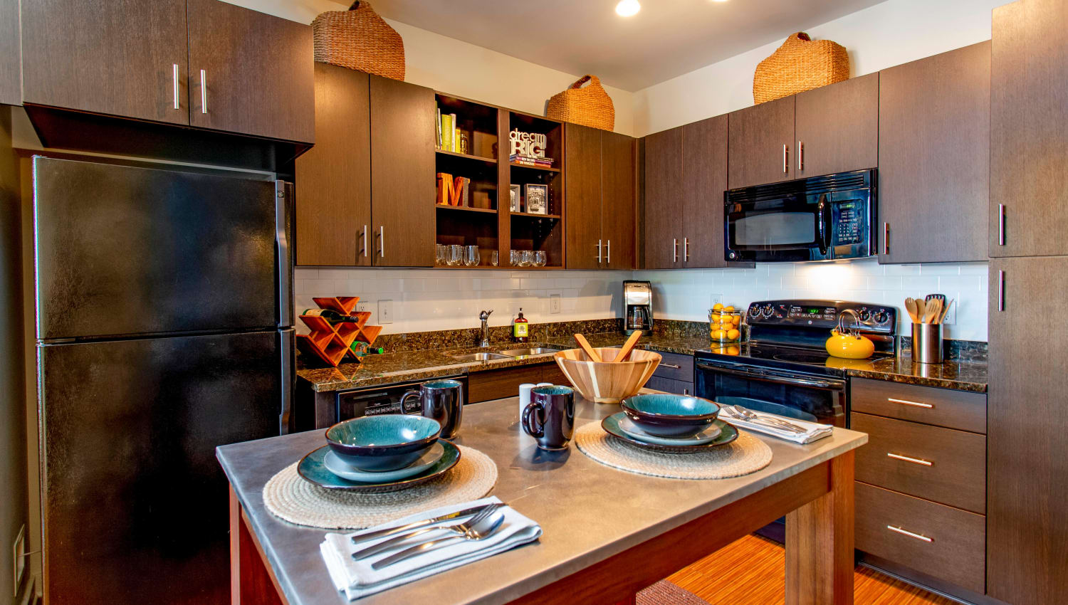 Gourmet kitchen with sleek black appliances and granite countertops in a model apartment at Olympus Midtown in Nashville, Tennessee