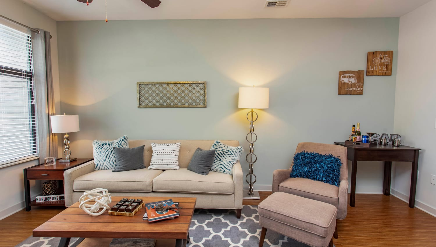 Accent wall and comfortable furnishings in a model apartment's living area at Olympus Midtown in Nashville, Tennessee