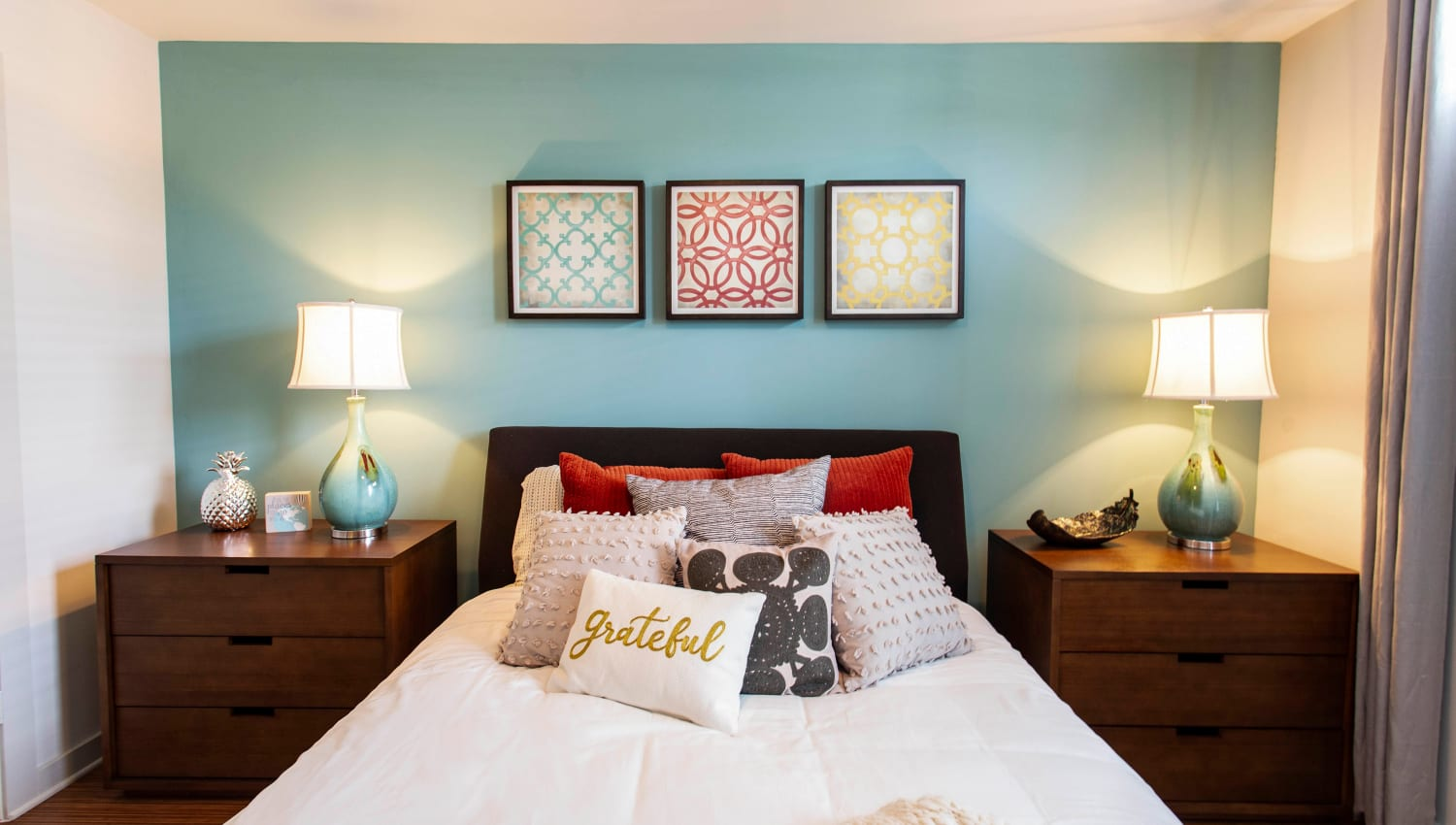 Well-furnished master bedroom in a model apartment at Olympus Midtown in Nashville, Tennessee