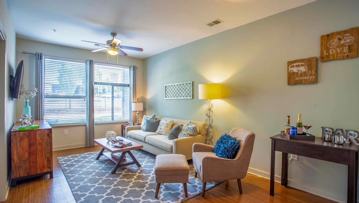 Ceiling fan and large bay windows in a model home's living area at Olympus Midtown in Nashville, Tennessee