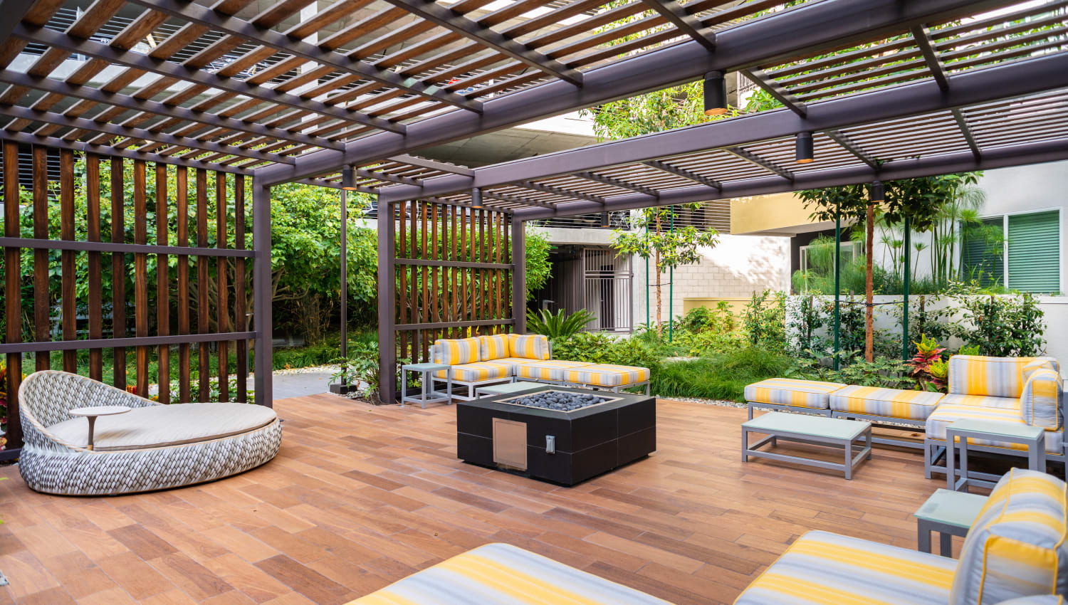 Large pergola covering an outdoor lounge and fire pit area at Fusion Apartments in Irvine, California