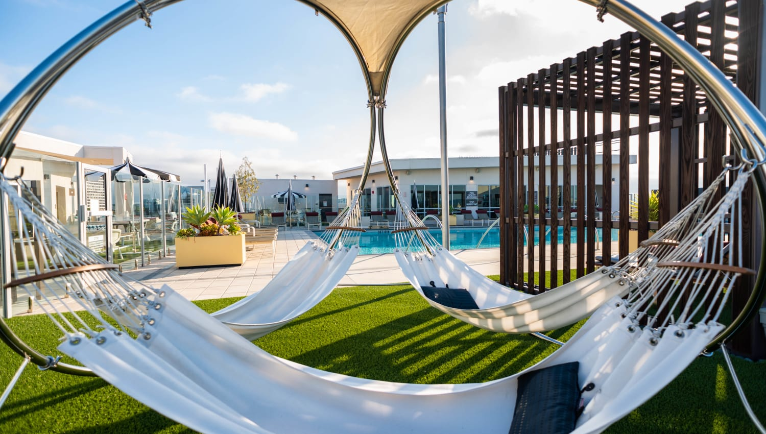 Shaded hammocks near the rooftop swimming pool at Fusion Apartments in Irvine, California