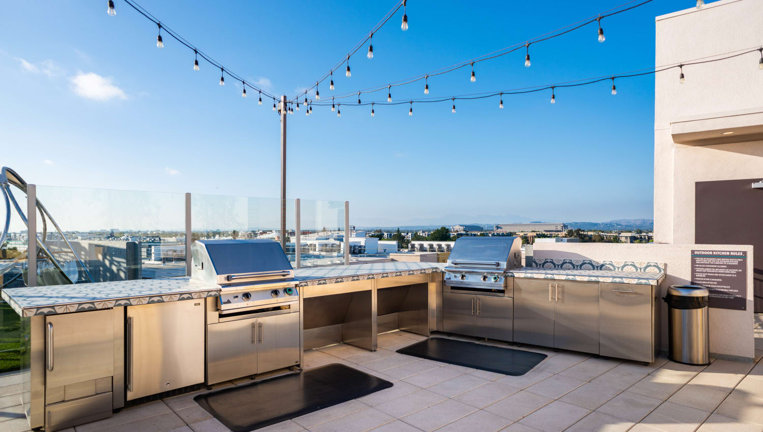 Rooftop barbecue area with gas grills at Fusion Apartments in Irvine, California