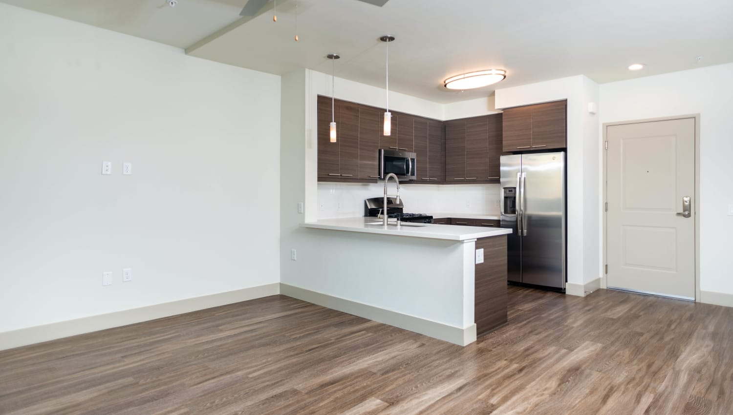 Hardwood flooring and a ceiling fan in the open concept living area of a model apartment at Fusion Apartments in Irvine, California