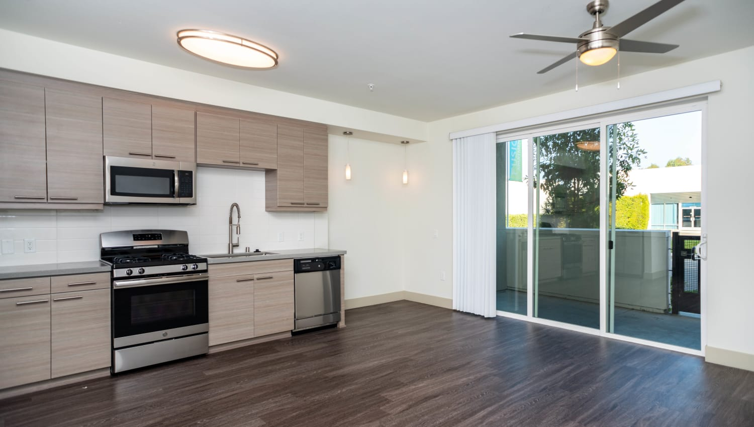 Ceiling fan near the kitchen and a sliding door to the private balcony outside a model home at Fusion Apartments in Irvine, California