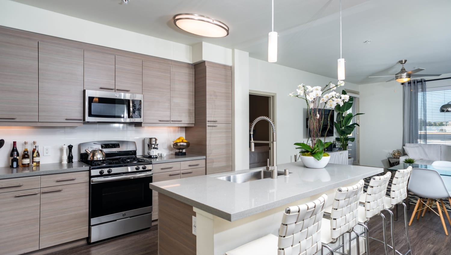 Custom wood cabinetry in a model home's open-concept kitchen at Fusion Apartments in Irvine, California