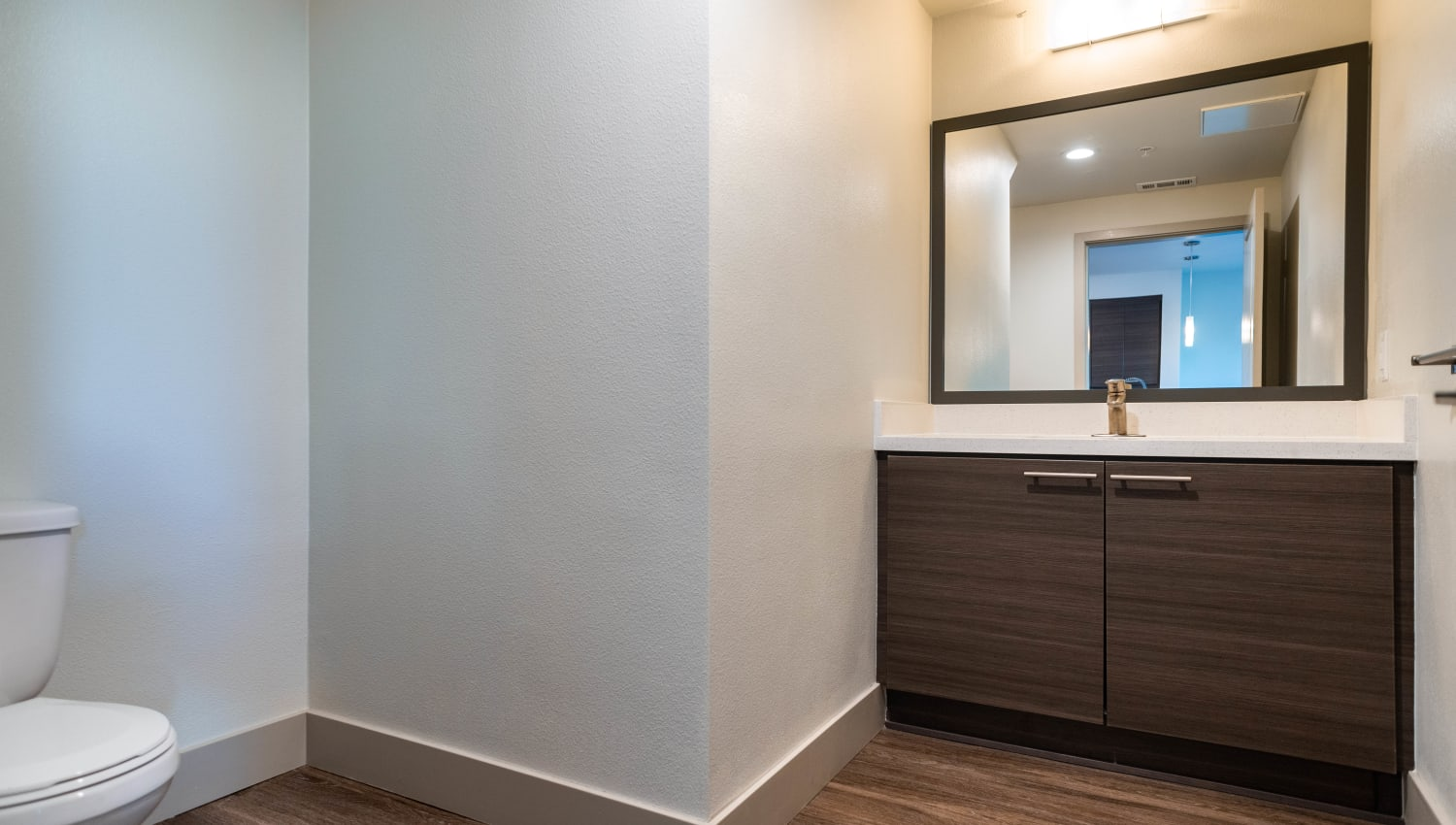 Custom wood cabinetry and a large vanity mirror in a model apartment's bathroom at Fusion Apartments in Irvine, California