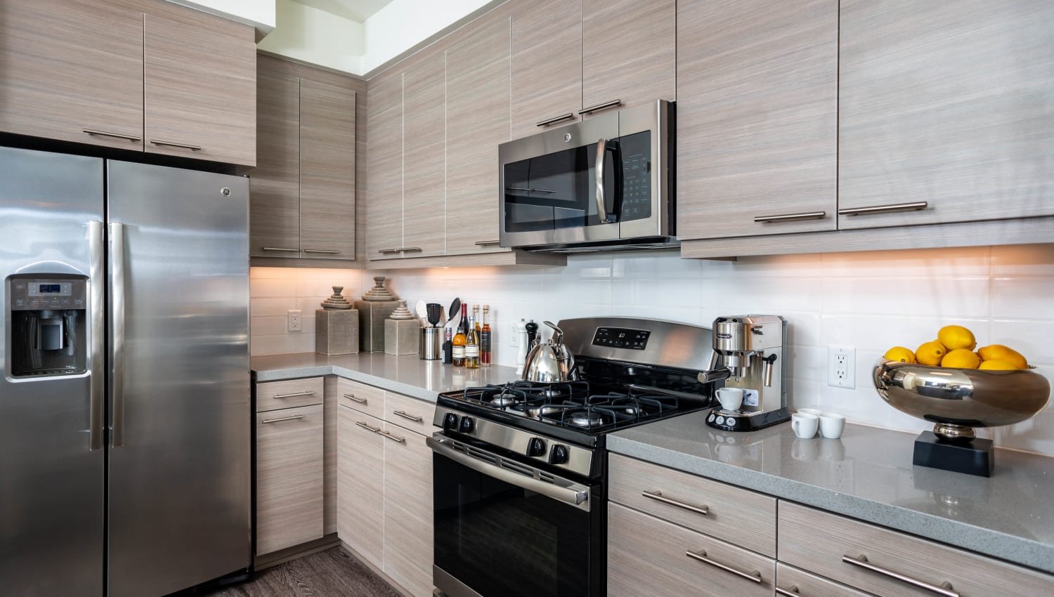 Stainless-steel appliances and quartz countertops in a model home's kitchen at Fusion Apartments in Irvine, California