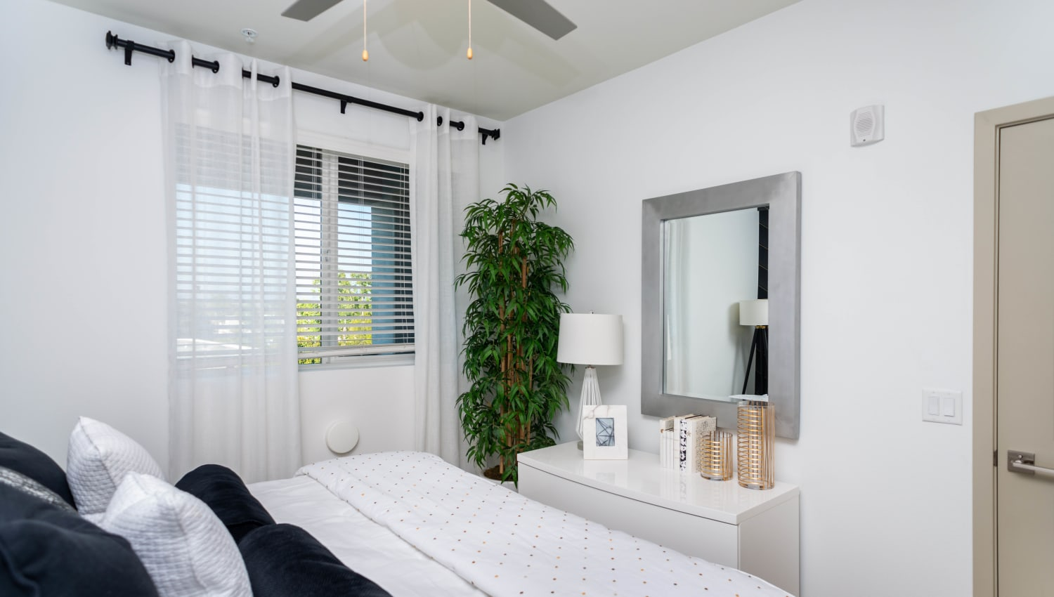 Ceiling fan in the well-furnished master bedroom of a model home at Fusion Apartments in Irvine, California