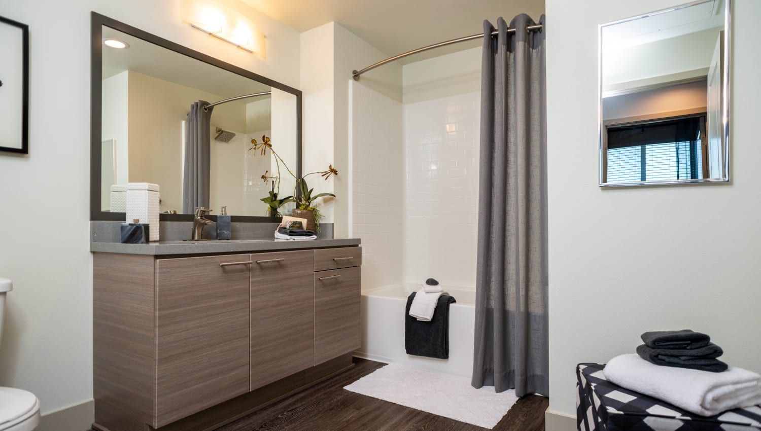Tiled shower and custom wood cabinetry in the master bathroom of a model home at Fusion Apartments in Irvine, California