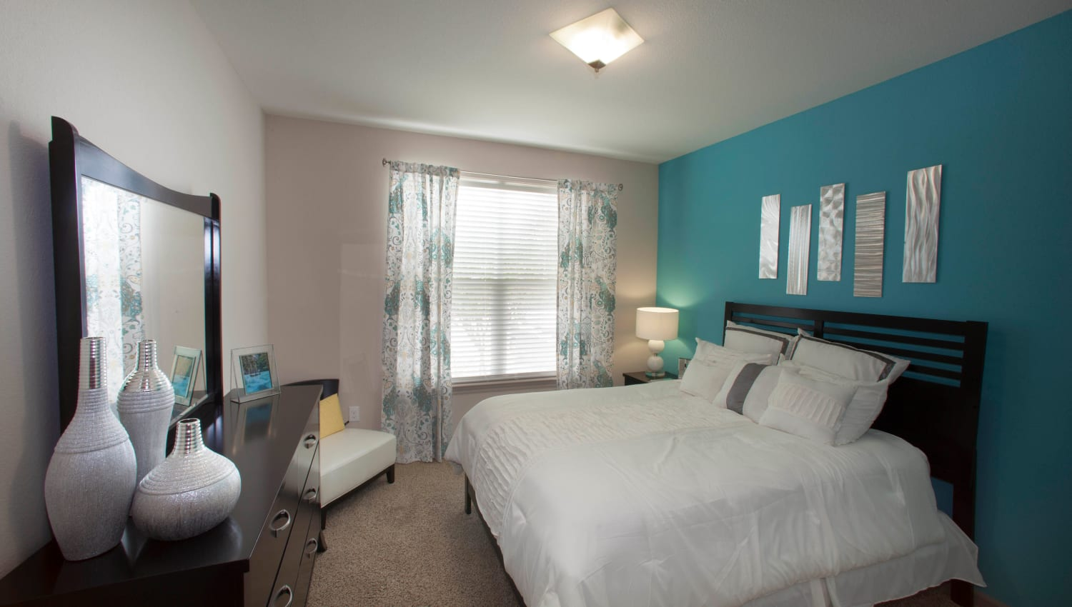 Plush carpeting and a large draped bay window in a model home's primary bedroom at Olympus Katy Ranch in Katy, Texas