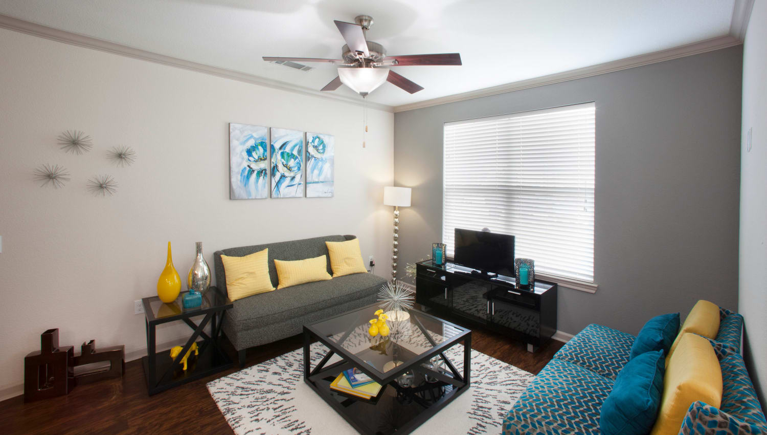Well-furnished living area with a large bay window in a model apartment at Olympus Katy Ranch in Katy, Texas