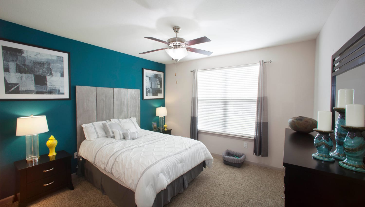Accent wall and a ceiling fan in a model home's primary suite at Olympus Katy Ranch in Katy, Texas