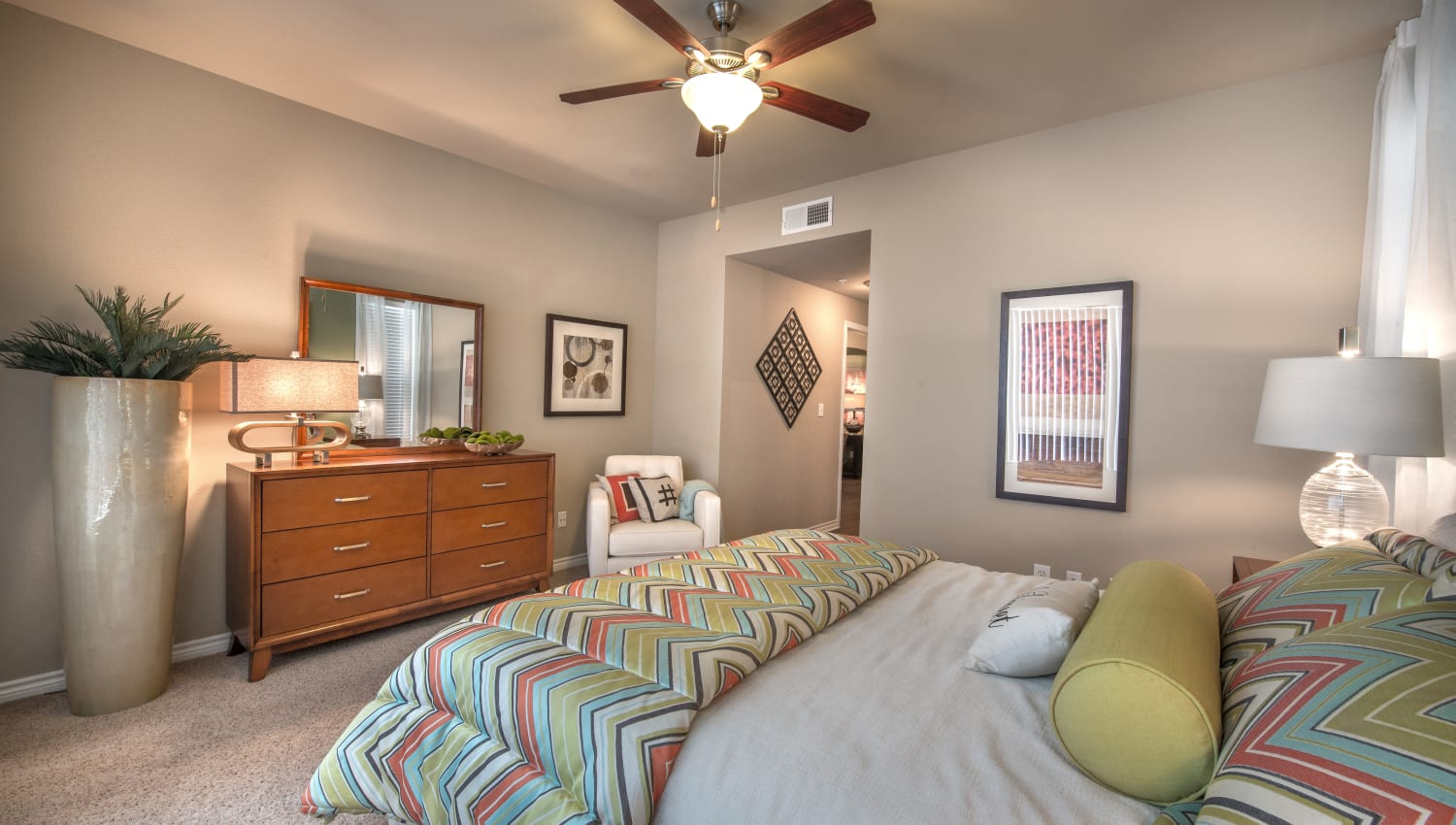 Well decorated comfortable bedroom at Olympus 7th Street Station in Fort Worth, Texas features a ceiling fan