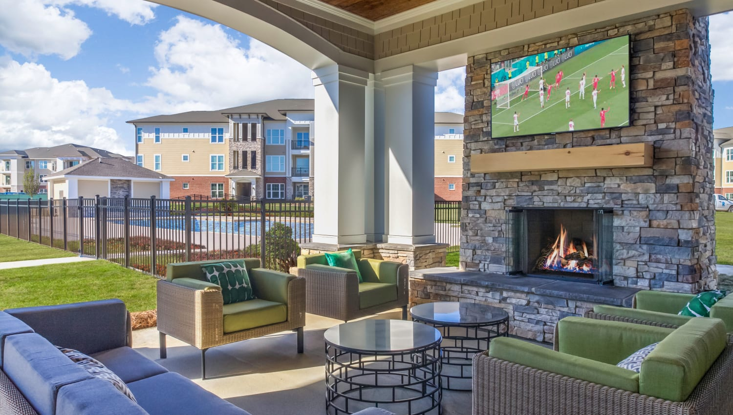 Outdoor cabaña with comfortable seating and a large flat-screen TV at The Palmer in Charlotte, North Carolina
