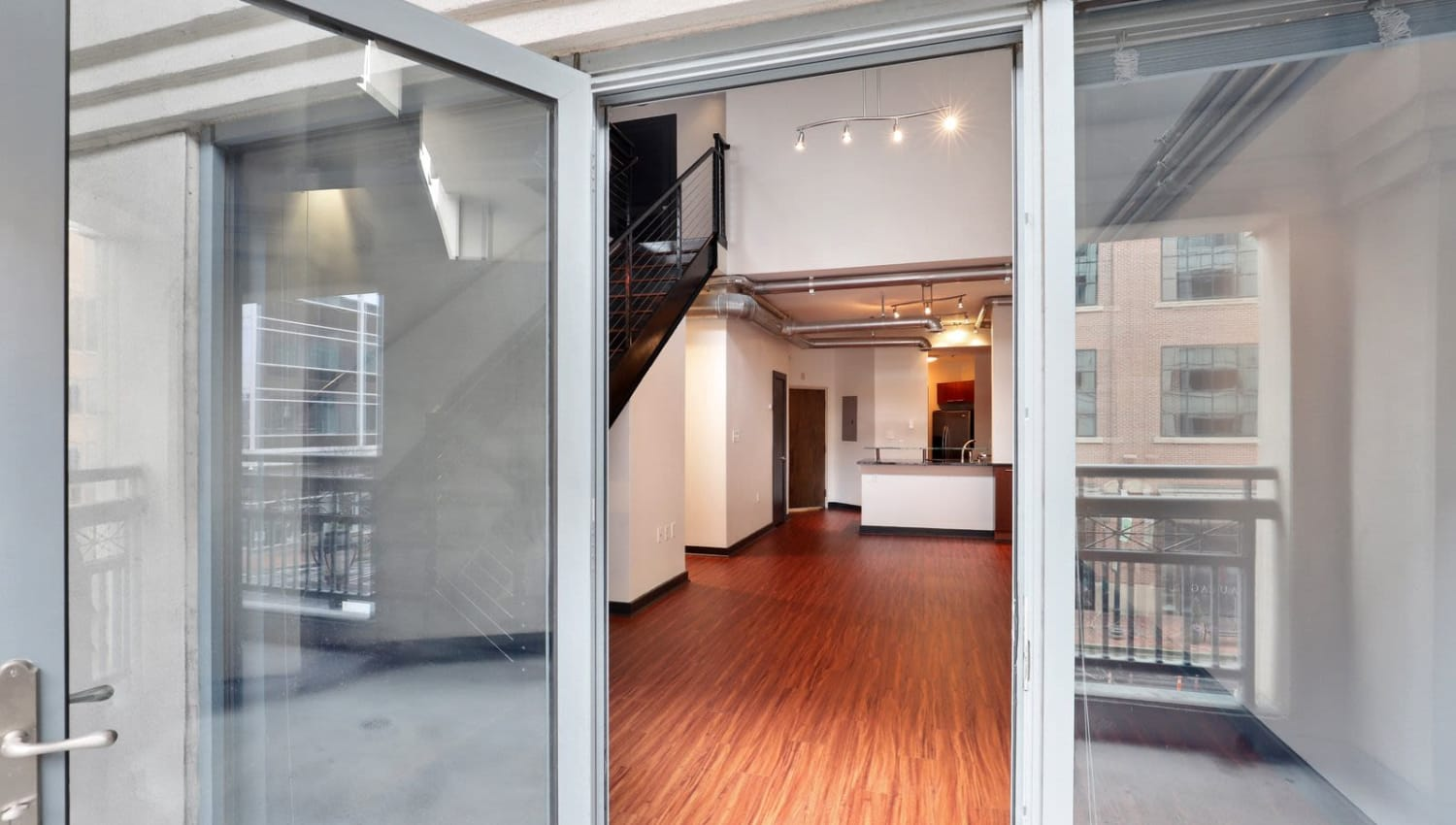 Living room with hardwood flooring and patio access at 17th Street Lofts in Atlanta, Georgia