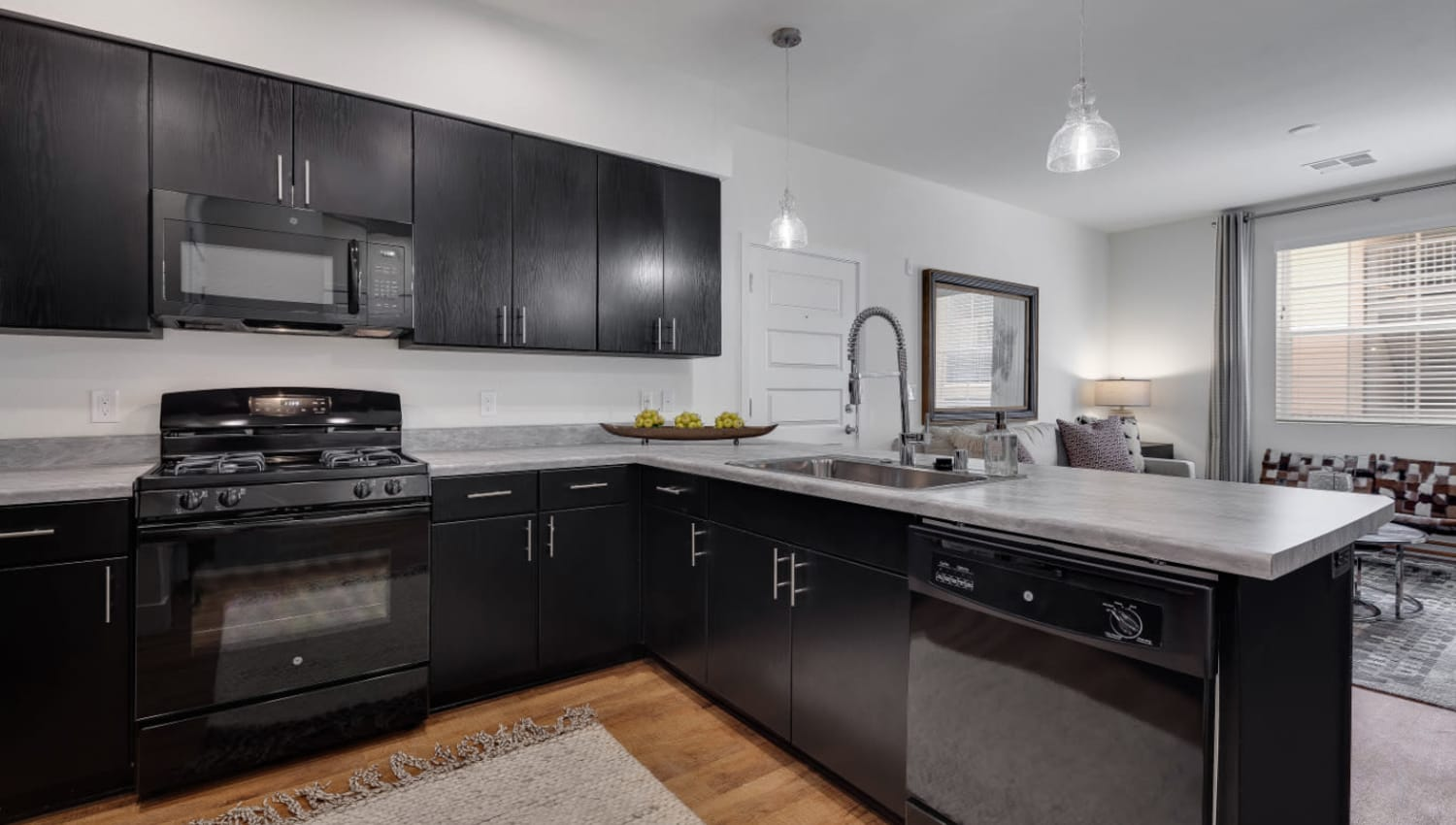 Quartz countertops and stainless-steel appliances in a model home's kitchen at Olympus Rodeo in Santa Fe, New Mexico