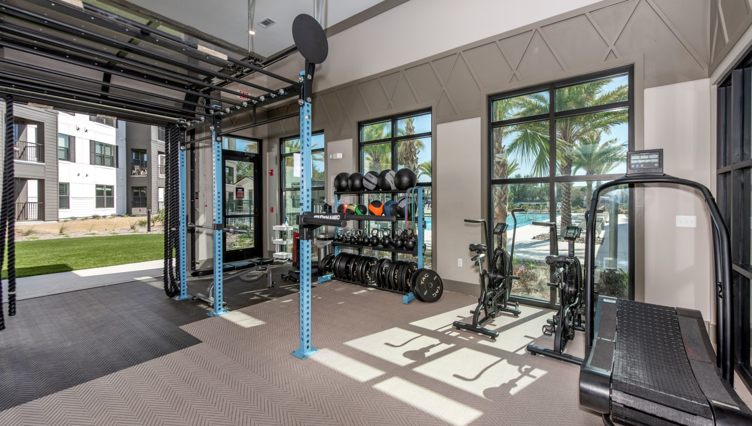A fitness center with a roll up door for hot summer days at Olympus Emerald Coast in Destin, Florida