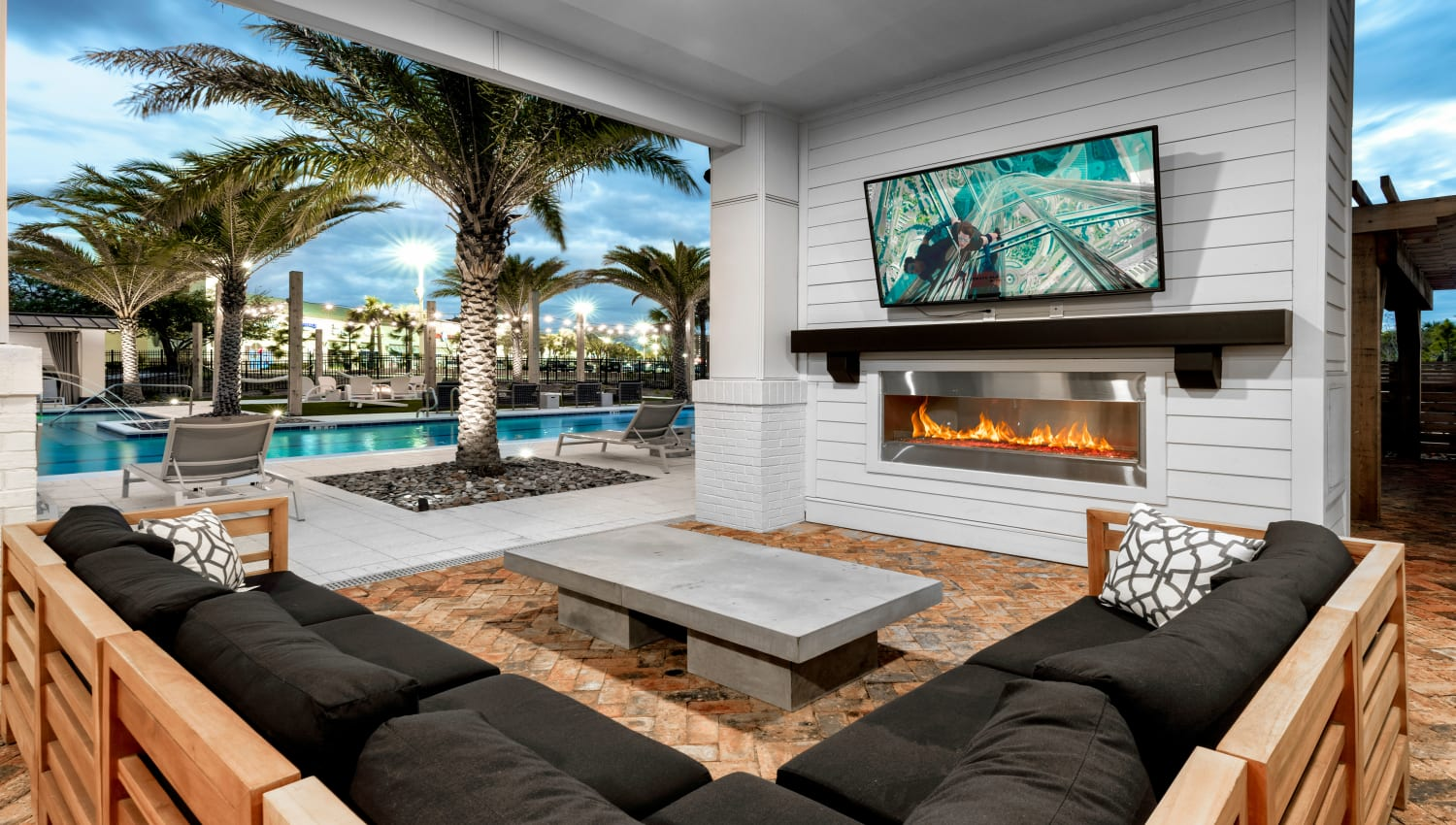 A covered lounge with comfortable seating and a flat-screen TV at Olympus Emerald Coast in Destin, Florida