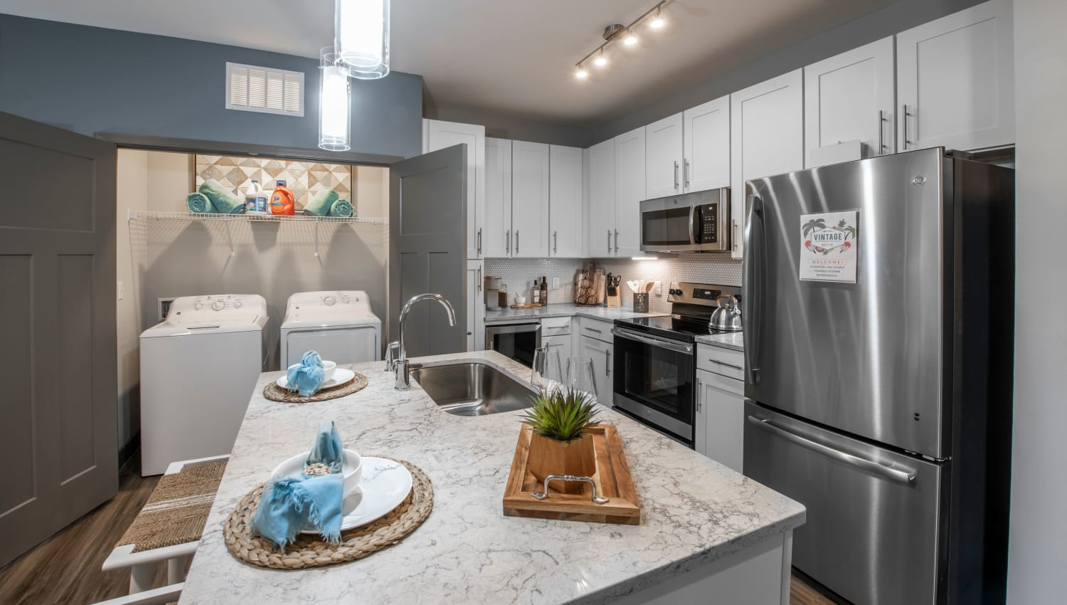 A kitchen with an adjacent washer and dryer closet at Olympus Emerald Coast in Destin, Florida