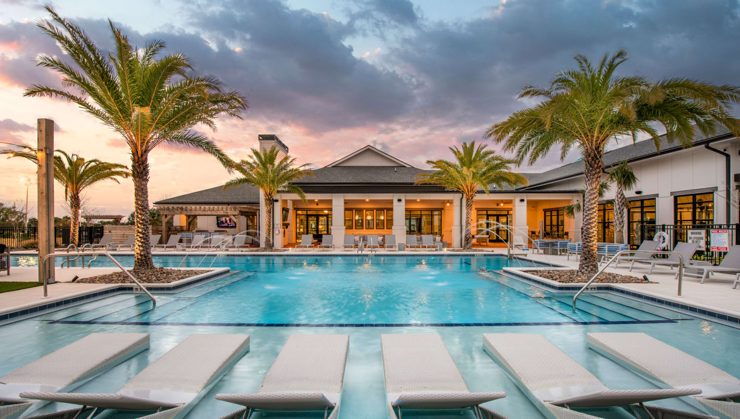 A resort-style swimming pool with plenty of lounge chairs at Olympus Emerald Coast in Destin, Florida