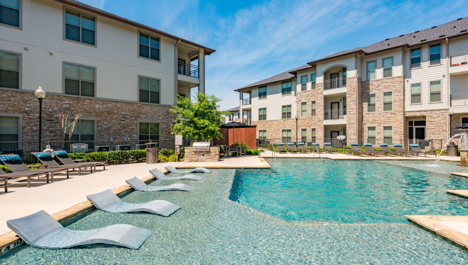 Dazzling blue pool with luxury lounge area at Olympus at Waterside Estates in Richmond, Texas