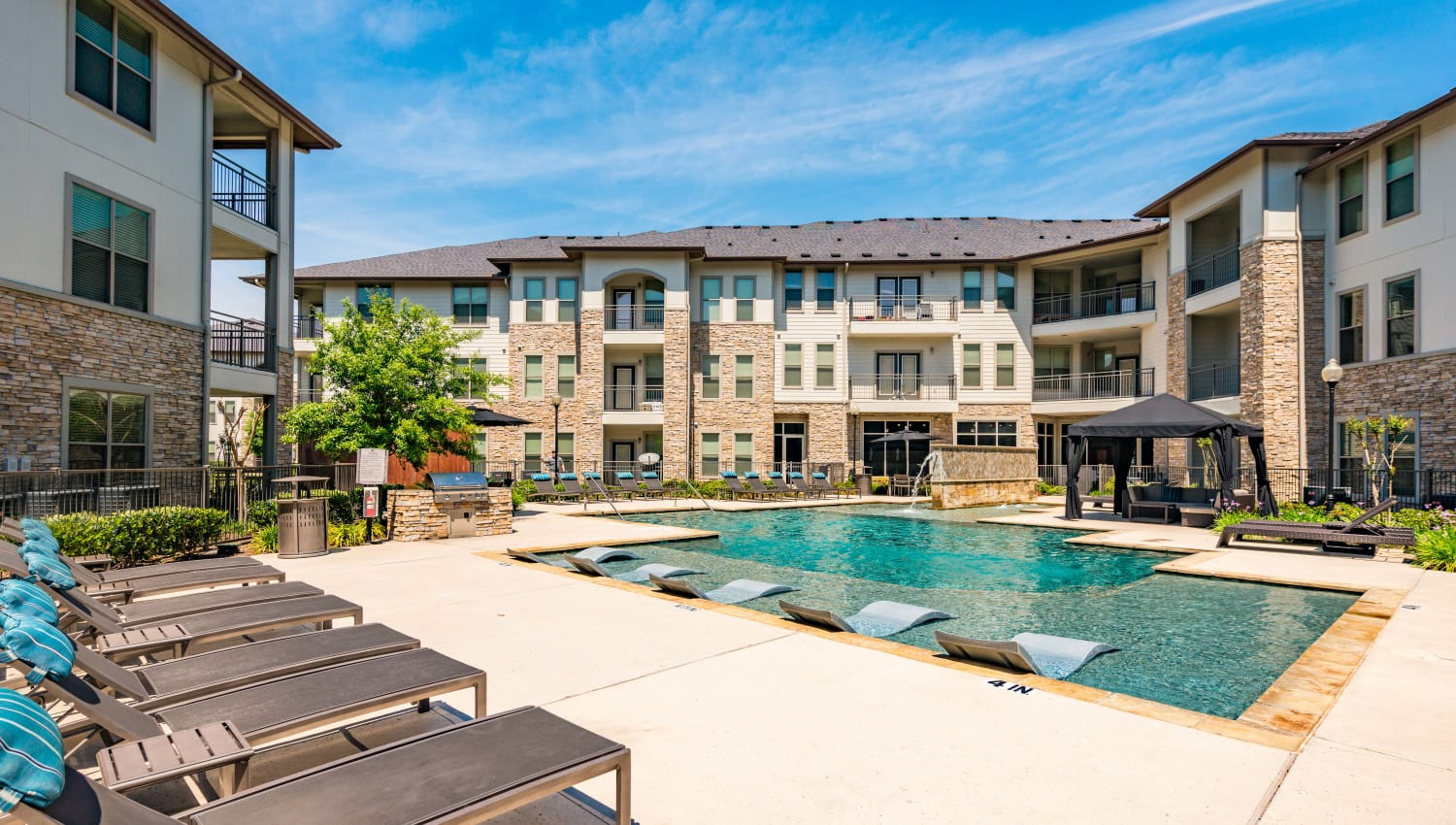 Outdoor lounge area around the pool at Olympus at Waterside Estates in Richmond, Texas