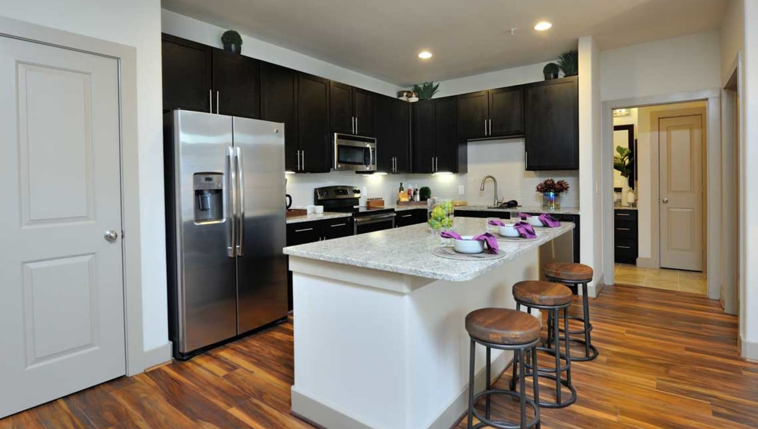 Model kitchen with granite island at Olympus Falcon Landing in Katy, Texas