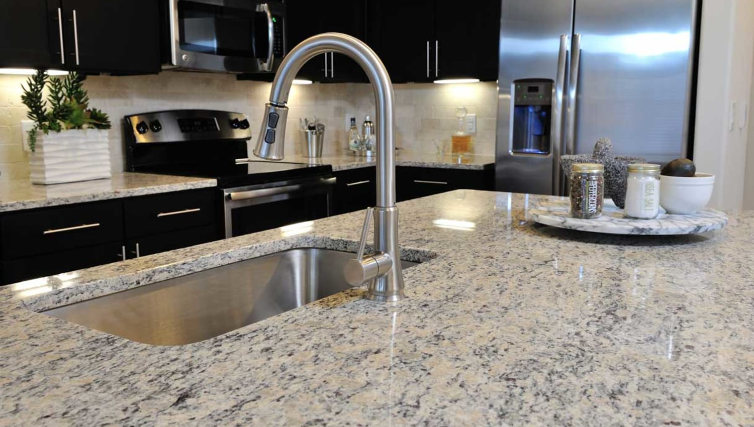 Granite counter island with stainless steel sink at Olympus Falcon Landing in Katy, Texas