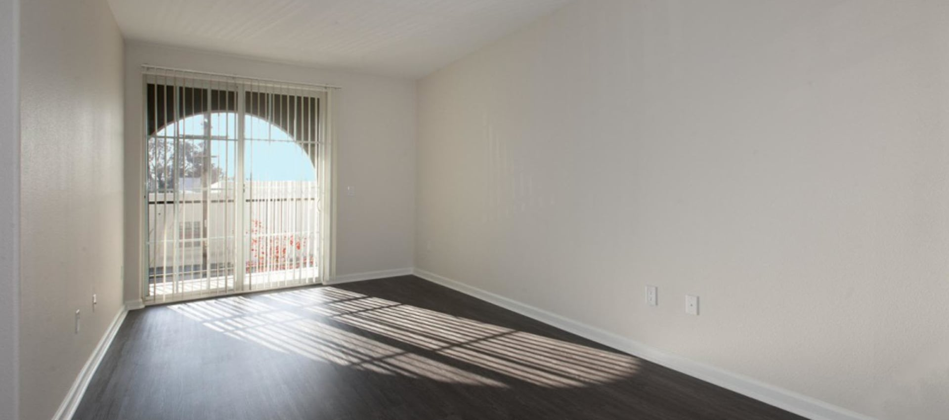 Hardwood floor in bright living room with large windows at Park Central in Concord, California