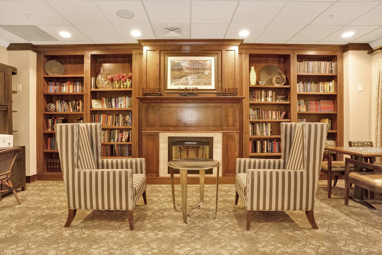 A library seating area next to the fireplace at The Inn at Greenwood Village