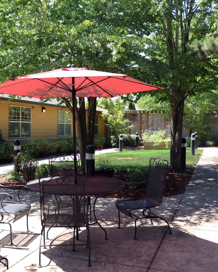 Vibrant and welcoming red umbrella with lawn furniture at The Springs at Willowcreek in Salem, Oregon
