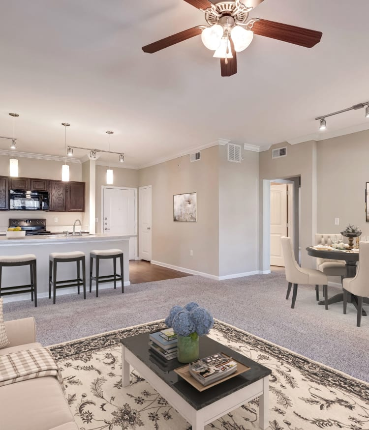 Partial view of the modern kitchen and living area in an open-concept floor plan at Overlook Ranch in Fort Worth, Texas