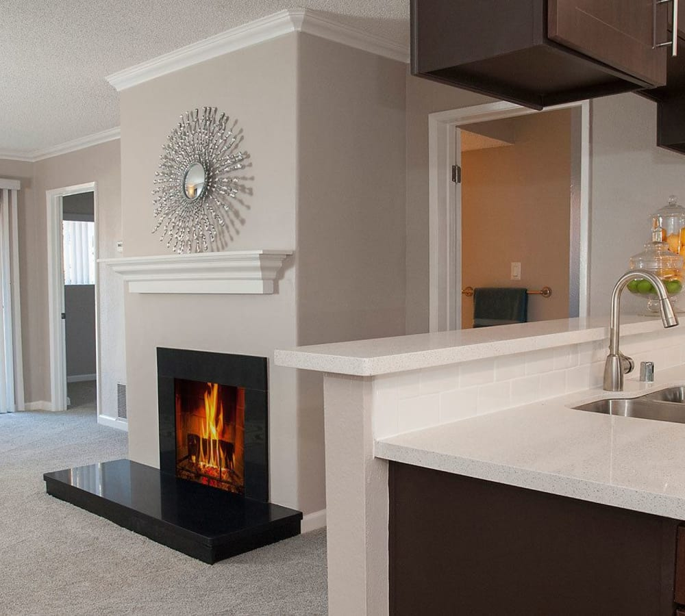 Living room with a fireplace at La Valencia Apartment Homes in Campbell, California