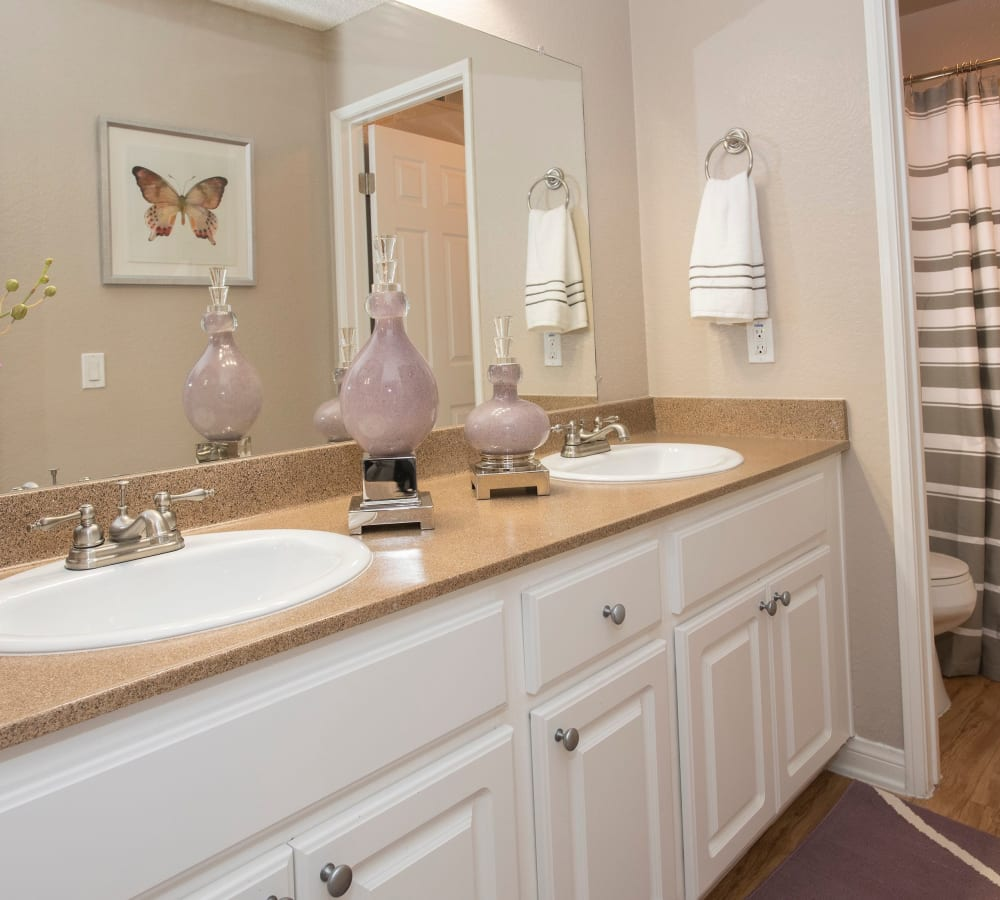 Bathroom with duel sinks and a large vanity mirror at Hidden Hills Condominium Rentals in Laguna Niguel, California