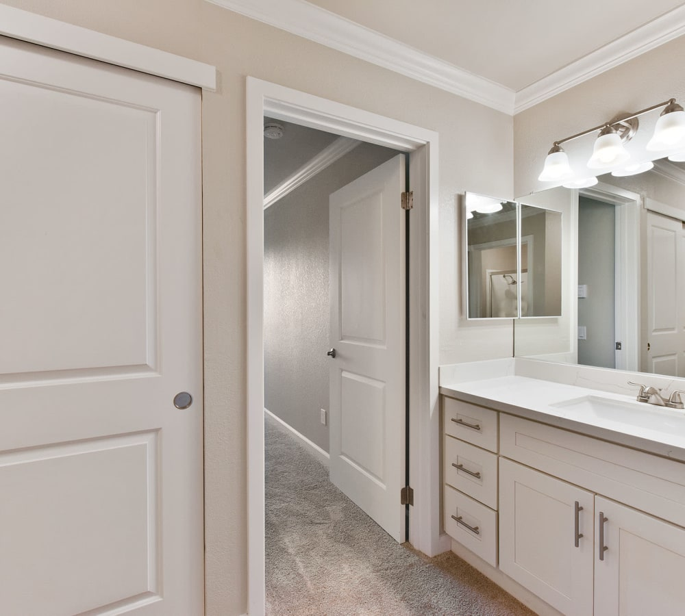 Beautiful white bathroom with a large vanity mirror at Tower Apartment Homes in Alameda, California