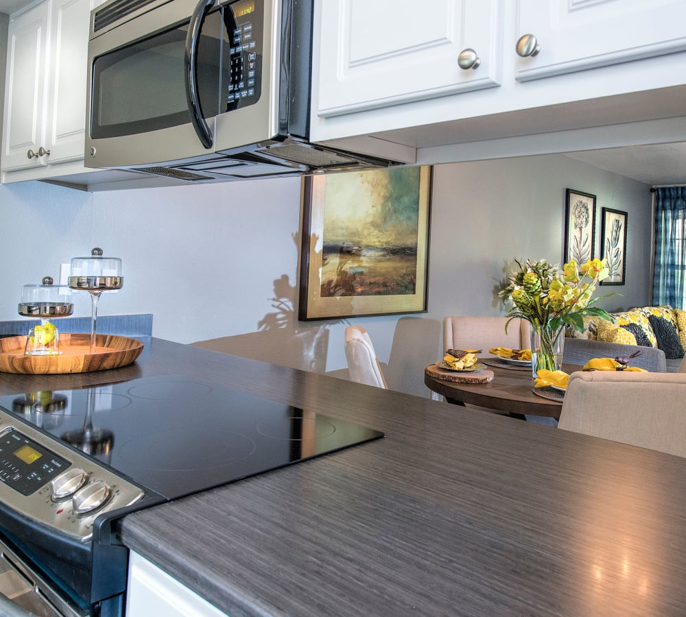Stainless-steel appliances with wooden cabinets at Slate Ridge at Fisher's Landing Apartment Homes in Vancouver, Washington
