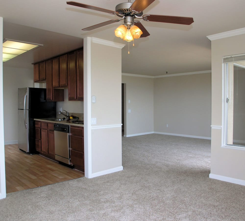 Spacious living room with a ceiling fan and plush carpeting at Tower Apartment Homes in Alameda, California