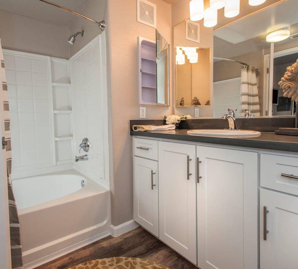 Master bathroom with a large vanity mirror at Venu at Galleria Condominium Rentals in Roseville, California