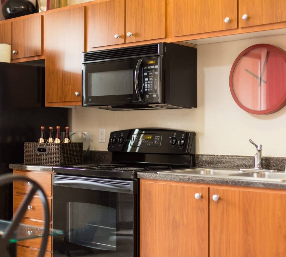 Kitchen with wood-style cabinetry with blank appliances at Venu at Galleria Condominium Rentals in Roseville, California