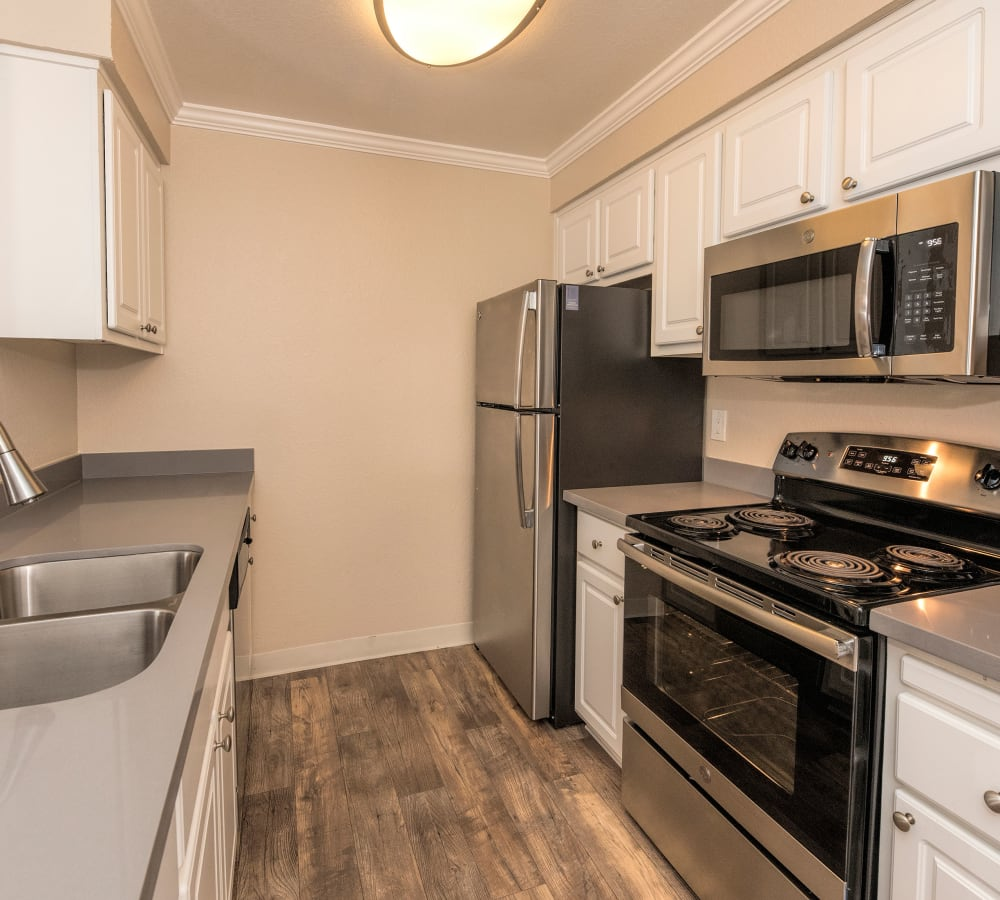 Kitchen with stainless-steel appliances and white cabinetry at Sterling Heights Apartment Homes in Benicia, California
